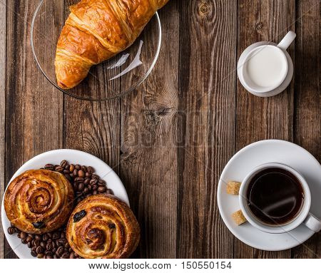 Coffee cup with milk jug, croissant and cinnabons on wooden background. Top view.