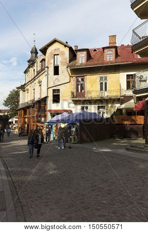 ZAKOPANE POLAND - SEPTEMBER 23 2016: Neglected facade of a historic building in the city center and several people who walk down the street can be seen in the distance.