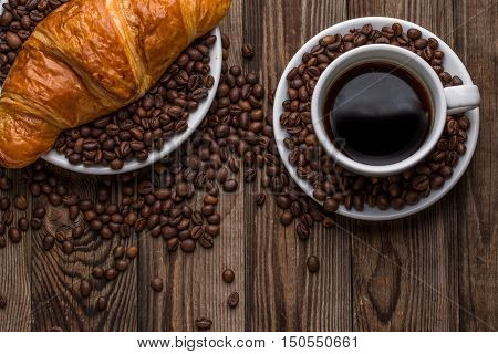 Breakfast coffee - cup and croissant with coffee beans on wooden background. Top view.