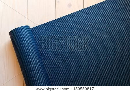 Dark blue mat for yoga pilates or fitness on wood background. Space for text.