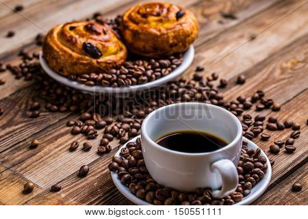 Coffee cup with coffee bean and cinnabons on wooden background. Breakfast background.