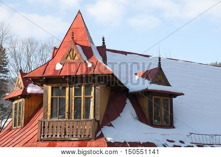 ZAKOPANE POLAND - JANUARY 04 2011: Painted in red sloping roof of the old dwelling house. Structural elements of the roof and the balcony is made in the style of architecture of the region