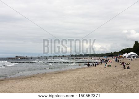 KOLOBRZEG POLAND - JUNE 26 2016: Several unidentified vacationers spend their spare time at the shoreline of the Baltic Sea during a cloudy day and they enjoy their stroll.