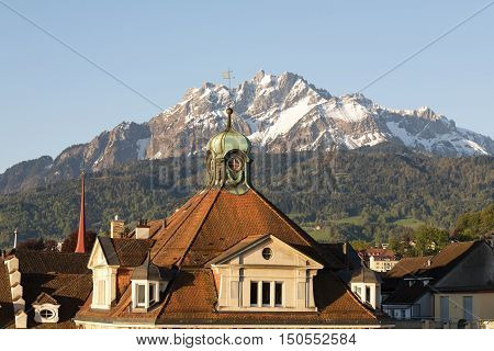 LUCERNE SWITZERLAND - MAY 06 2016: Sloping roof covered with tiles of a historic building shows a proximity of the city to the snowy peak of Pilatus one of the most well-known peaks in Switzerland