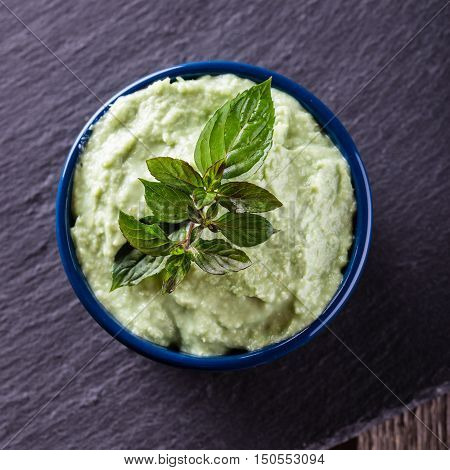 Top View On Bowl With Wasabi Dip With Piece Of Herb