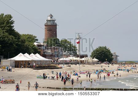 KOLOBRZEG POLAND - JUNE 19 2016: massive lighthouse that was built of brick dominates over the beach. Sandy beach by the Baltic Sea and many vacationers can be seen there.
