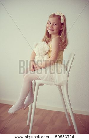 Pretty Smiling Ballet Girl In White-yellow Tutu Sitting On Chair With Her Bear