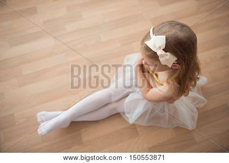 Pretty Diligent Ballet Girl Sitting In White Tutu At Dance Studio