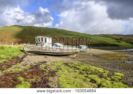 Sun shines on the peeling paint of two old abandoned wooden boat wrecks on the shore of Loch Harport on Isle of Skye Scotland