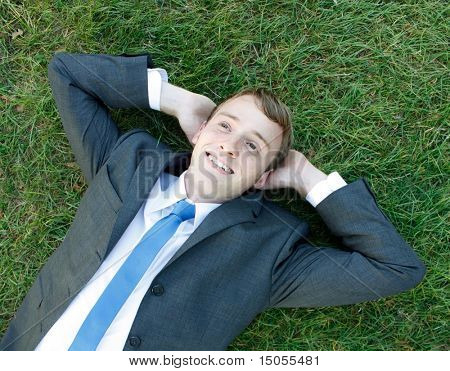 A business man lying on the grass
