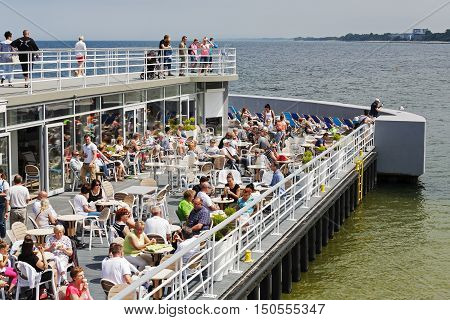 KOLOBRZEG POLAND - JUNE 19 2016: Unidentified vacationers spend a good time relaxing at the cafe that is placed at the end of the pier many of them enjoys of magnificent views