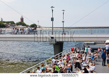 KOLOBRZEG POLAND - JUNE 19 2016: Unidentified vacationers enjoy the cafe placed at the end of the concrete pier other people are resting or are walking along the jetty