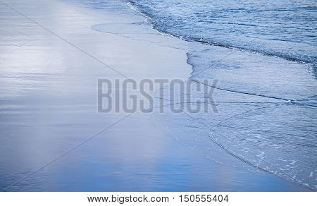 Waves and wet sand reflecting a blue sky