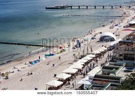 KOLOBRZEG POLAND - JUNE 22 2016: Unidentified vacationers enjoying the sunbathing and strolling along the Polish coast of the Baltic Sea.