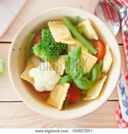 Rustic soup with fresh vegetables and ravioli