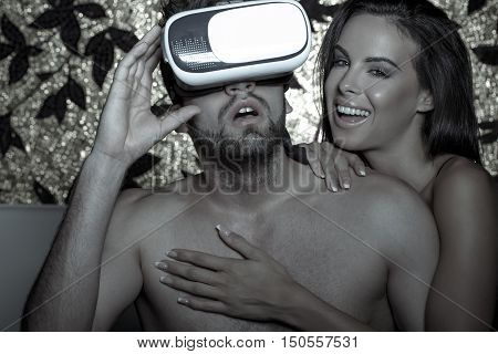 Young excited man in VR glasses with girlfriend foreplay at night