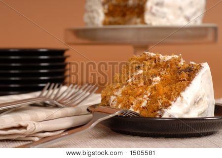 Carrot Cake With Forks, Plates, And Whole Cake In Background