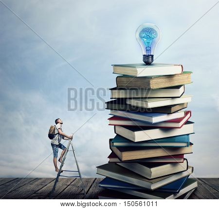 Young boy on the ladder with a bag on his back trying to climb a pile of books looking for a lightbulb. In search of knowlegde concept.