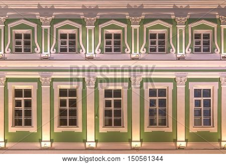 Several windows in a row on night illuminated facade of Saint Petersburg State University front view Russia