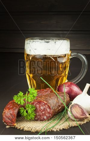 Glass of beer and sausages on a wooden background. Relax with a good beer.