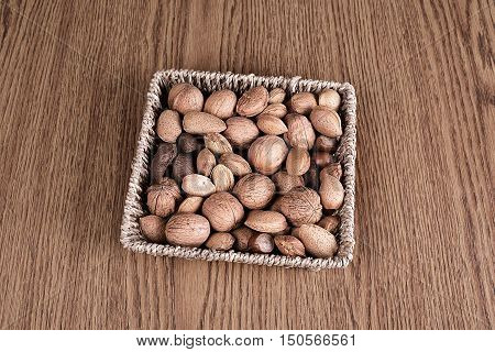 Different types of nuts in basket on wooden background