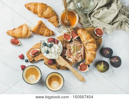 Breakfast with croissants, homemade ricotta cheese, figs, fresh berries, prosciutto, honey and espresso coffee on rustic serving board over white marble background, top view, horizontal composition