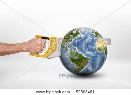 Man's hand sawing a globe with a saw. Destruction of the planet. Anthropogenic impacts. Environmental effects. Harm and damage. Elements of this image are furnished by NASA.