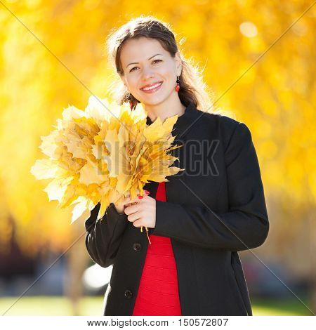 Young woman walking in the autumn park. Beauty nature scene with colorful foliage background, yellow trees and leaves at fall season. Autumn outdoor lifestyle. Happy smiling woman enjoy the fall