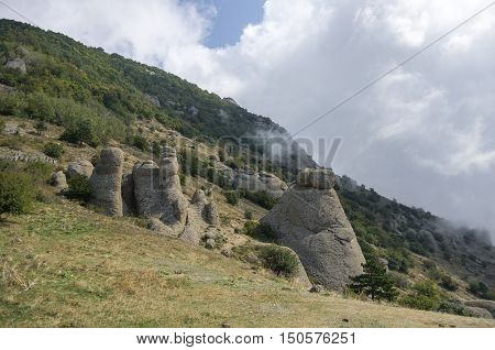 Low Clouds On Slope Of The Demerdji Mountain. The Rock Formations In Valley Of Ghosts. Landscape Of