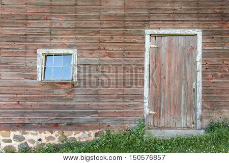 Section of a weathered building showing a door and single pane window. Textured wood with faded red grey and white framing.