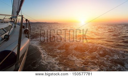 Stunning sunset with a yacht in the Aegean sea.