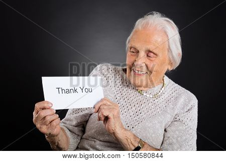 Portrait Of Smiling Elder Woman Showing Thank You Card Over Grey Background