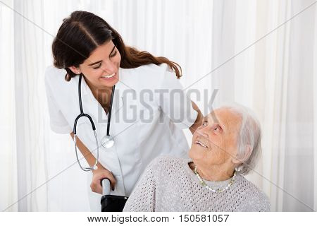 Caring Female Doctor Helping Handicapped Senior Patient In Hospital