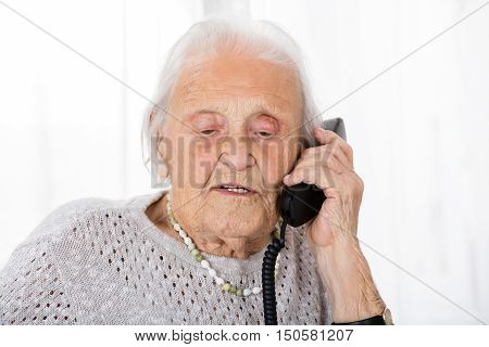 Portrait Of Senior Woman Having Conversation On Landline Phone