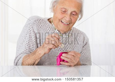 Happy Senior Woman Inserting Coin In Small Purse
