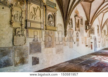 Augsburg, Germany - September 08, 2016: Religious icons and placards from old times on wall in old German church with gothic architecture