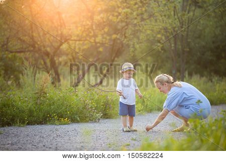 Cute little toddler boy watching his mother drawing on the raod. Mom and son on sunset walk in the park. Lifestyle and motherhood concept