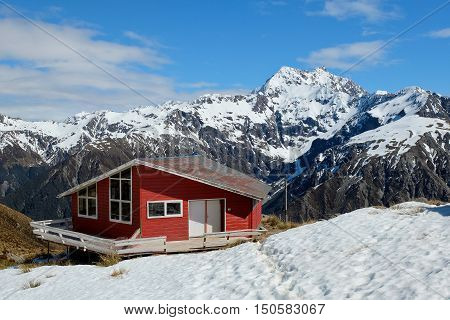 A Bright Red Hut Among Snowy Mountains.  Temple Basin, Arthurs Pass, Southern Alps, New Zealand