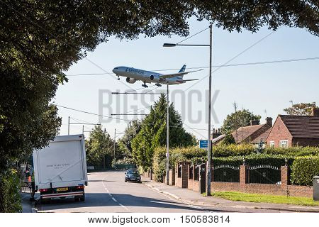 LONDON HEATHROW UK - 03 OCTOBER 2016: American Airlines plane approaching to London Heathrow airport low above housing estate.