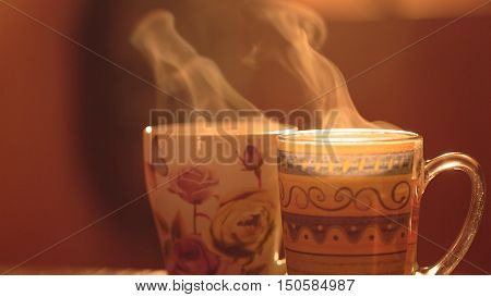 Steam from the mugs. Hot invigorating drink in a cup on a background of the early morning sun warm