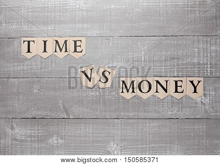 time vs money paper letters symbol motivation sign on wooden board