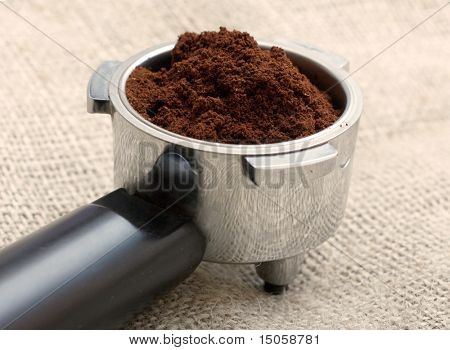 An espresso handle filled with ground coffee