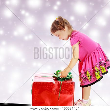 Cute little girl in a pink dress, turned sideways and bent over a large box with a gift. The girl unties the bow.On new year's or Christmas purple background where glowing large white star.
