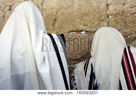 Jewish Men are praying wrapped in talit at the western wall in the old city in Jerusalem Israel