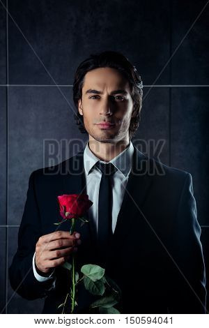 Portrait Of Handsome Young Boyfriend Holding Red Rose