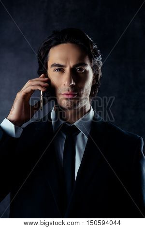 Portrait Of Successful Young Businessman Talking On Mobile Phone