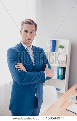 Portrait Of Successful Serious Businessman With Crossed Hands In Office