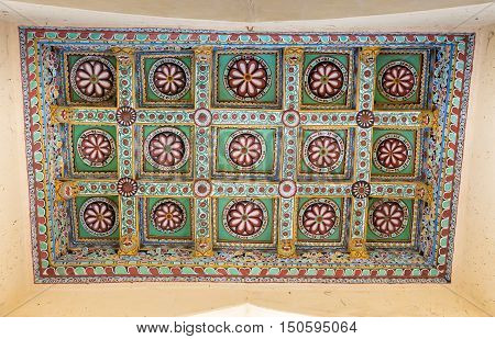 Madurai India - October 21 2013: Shot on the abundant decoration of one rectangular ceiling at Nayak Palace. Cream with wine-colored lotus images and green backgrounds.
