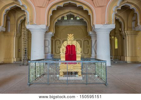 Madurai India - October 21 2013: Copy of the golden throne of the Nayak at main audience hall of his palace. Fence shields throne from public.
