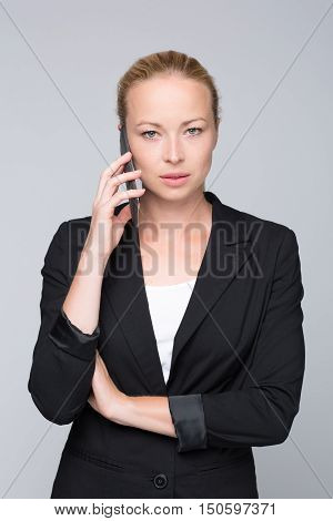 Beautiful young caucasian businesswoman in business attire talking on mobile phone. Studio portrait shot on grey background.